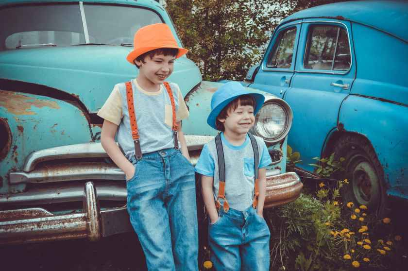 two boys leaning on classic teal vehicle